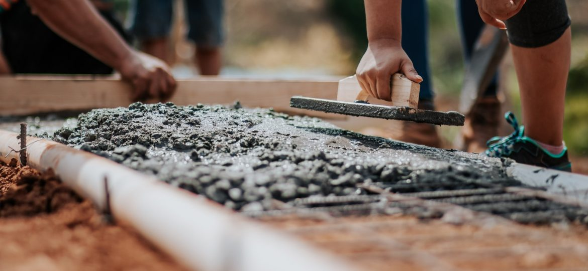 Two people laying concrete and smoothing it out with a trowel